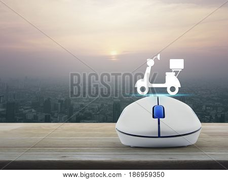 Motor bike icon with wireless computer mouse on wooden table over modern city tower at sunset vintage style Business internet delivery service concept