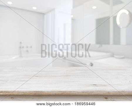 Background of blurred bathroom interior with wooden table in front