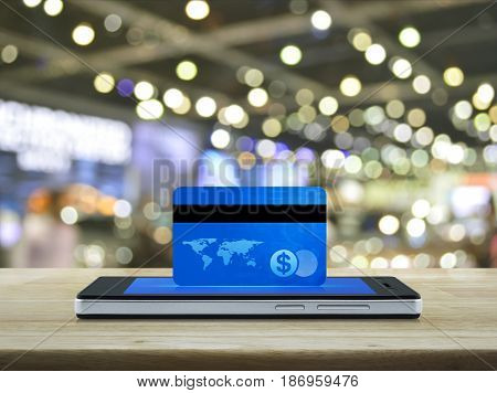 Blue credit card on modern smart phone screen on wooden table over blur light and shadow of shopping mall Online e-payment concept Elements of this image furnished by NASA