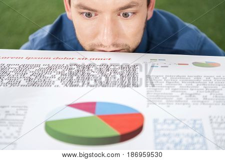Young Businessman Looking At Documents With Business Charts And Diagrams, Business Establishment