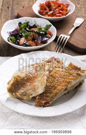 Fried rose fish fillet on a white plate. Sebastes norvegicus or ocean perch.