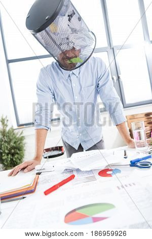 Portrait Of Businessman With Trash Bucket On Head In Office, Business Establishment