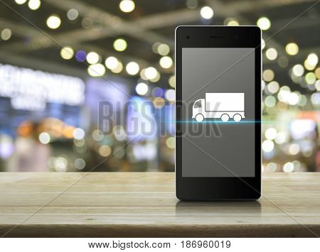 Truck flat icon on modern smart phone screen on wooden table over blur light and shadow of shopping mall Business transportation service concept