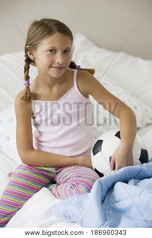 Caucasian girl sitting on bed with soccer ball