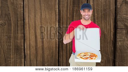 Digital composite of Smiling delivery man showing pizza against wooden wall