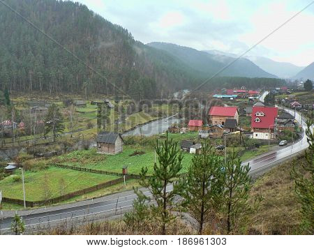 Small village in the valley between the mountains. Cloudy rainy autumn day. Road at the front, hills at the horizon. Rural landscape. Altai region, Russia.