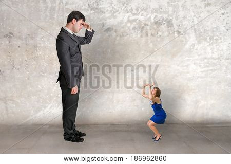 Big businessman and small businesswoman watch each other - unequal competition concept