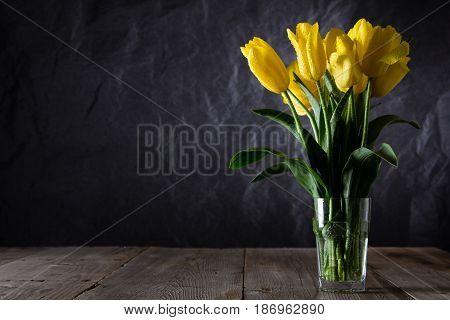 Bouquet of beautiful fresh yellow tulips in dew on dark background. Still life photo