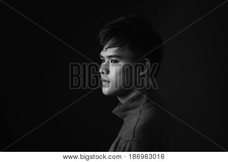 Attractive Asian Man Looking Down To His Side On Dark Studio Background.