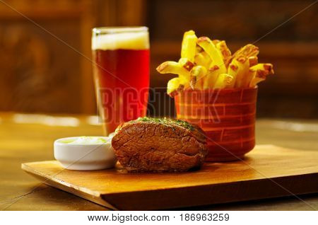 Delicious beef flank steak with ketchup, french fries and a glass of beer on wooden board.