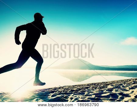 Tall Fit Man Running Along The Sea Shore In Morning. Healthy Male Jogging On Beach.