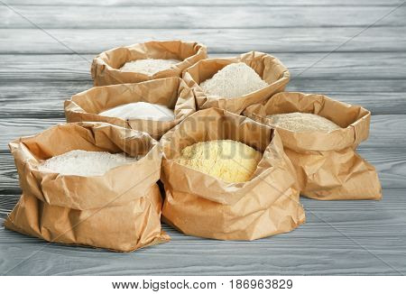 Bags with different types of flour on wooden background