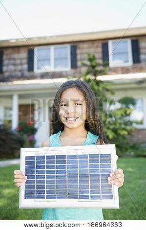 Hispanic girl holding solar panel