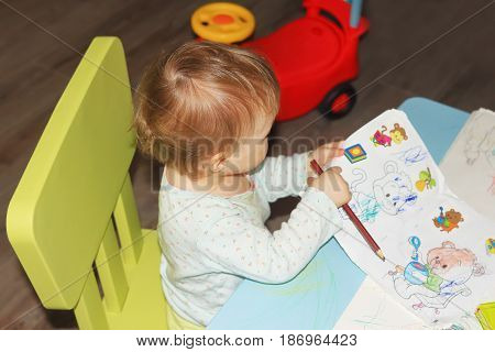 A little girl draws an ornament and drawings with pencils on a children's table. The art of young children in the form of drawings.