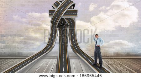 Digital composite of Confused businessman standing on tangled highway