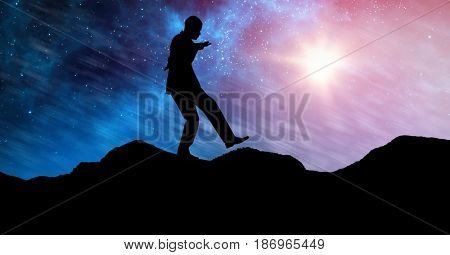 Digital composite of Silhouette businessman balancing on mountain against sky at night