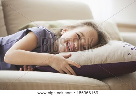 Smiling Caucasian girl laying on sofa