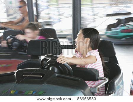 Girl driving bumper cars in amusement park