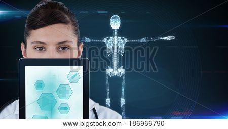 Digital composite of Portrait of doctor showing medical icons on tablet PC with skeleton in background