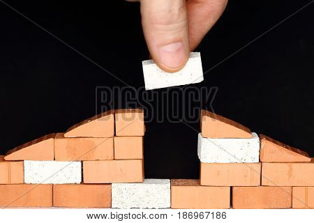put a brick in a wall of a house