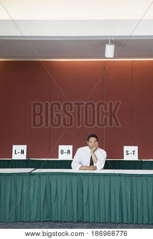 Bored African American businessman sitting at registration desk