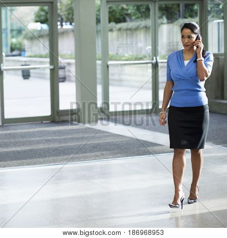 Black businesswoman talking on cell phone in lobby