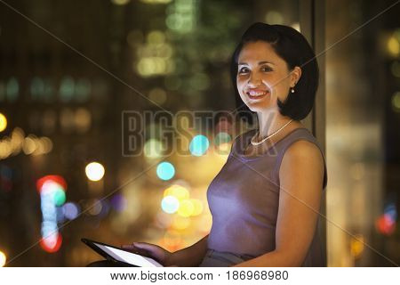 Mixed race businesswoman using digital tablet at night