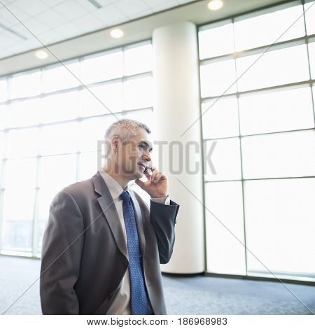 Caucasian businessman talking on cell phone in lobby