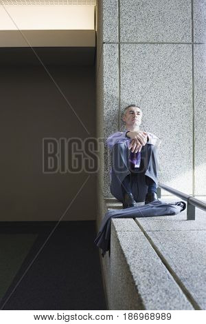 Caucasian businessman relaxing on office ledge