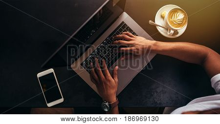 Close up shot of young man sitting at coffee shop and working on laptop. Focus on hands typing on laptop keyboard with mobile phone and cup of coffee on table.