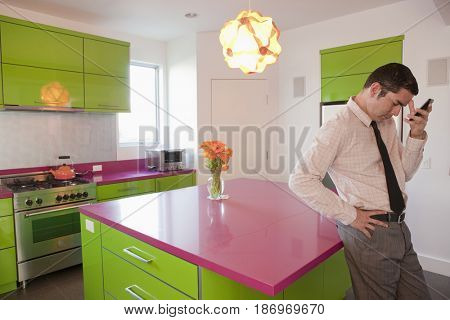 Hispanic businessman text messaging on cell phone in kitchen