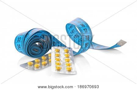 Diet concept. Measuring tape and blister packages of pills on white background