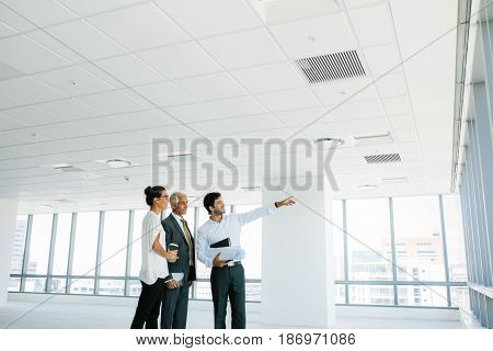 Real estate broker showing office space to clients. Business people and real estate agent at empty office space with estate broker pointing at something interesting.