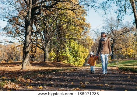 mother and daughter happy standing in the autumn park