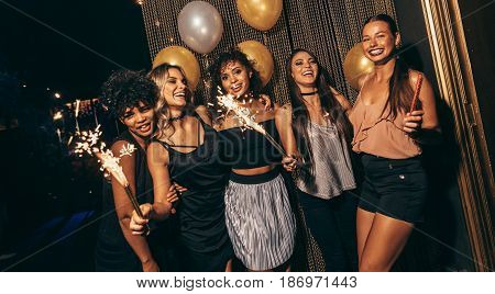 Happy multiethnic friends holding sparkling sticks at nightclub. Young people having fun at disco.
