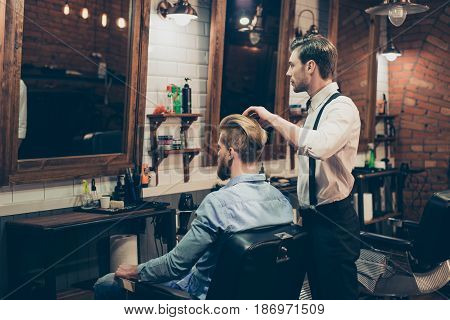 Barber Shop Classy Dressed Stylist Is Working For A Perfect Hairdo Of A Blond Bearded Guy In Caual J