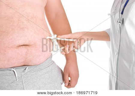Female doctor measuring fat on man's belly using caliper on white background, closeup. Weight loss concept