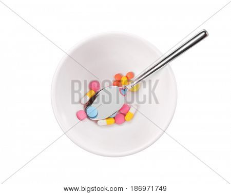 Diet concept. Spoon in bowl with assorted pills on white background