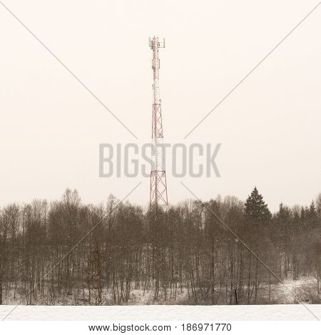 Telecommunication tower in the forest, winter landscape