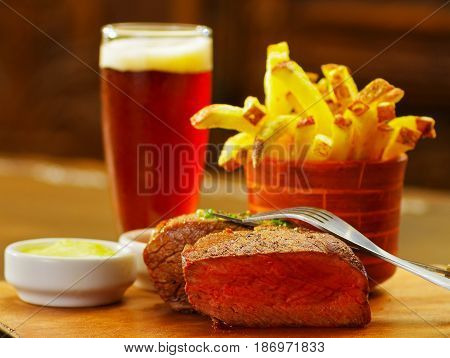 Close up of a well-done grilled marinated beef flank steak with ketchup, mustard and french fries with a glass of beer, with a fork over the meat on wooden board.