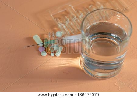 Medical ampoules, tablets and syringes on a peach background.