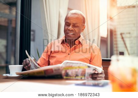 Businessman in a  beautiful cafe reading newspaper