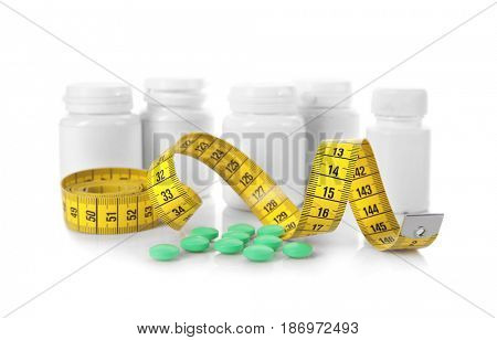 Diet concept. Measuring tape and plastic bottles with pills on white background