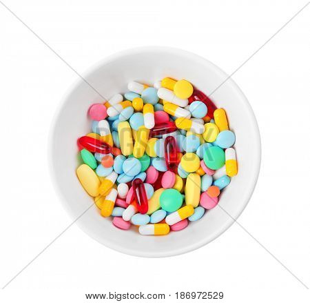 Diet concept. Bowl with colorful assorted pills on white background