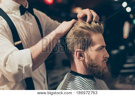 Red bearded guy is reading a magazine in a barber shop while getting bren new haircut from a classy dressed stylist. Both are buzy
