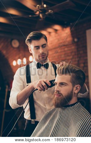 Beard Styling For A Handsome Young Guy At The Barber Shop. Hairdresser Is Attractive And Wearing Cla