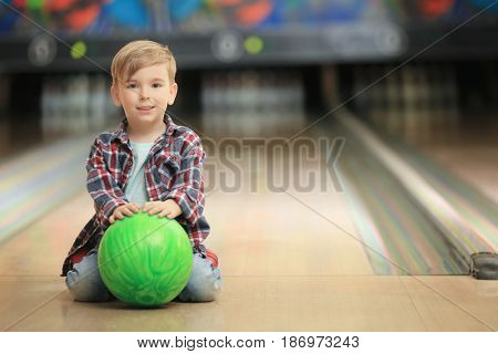 Cute little boy with ball sitting on floor in bowling club