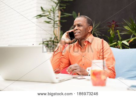 Businessman in a cafe, talking on mobile closeup picture