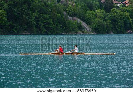 THUNERSEE ( LAKE THUN) SWITZERLAND - JUNE 13 2013: Pair of tourist rowing in kayak (racing boat) on Thunersee ( Lake Thun) at Spiez Switzerland
