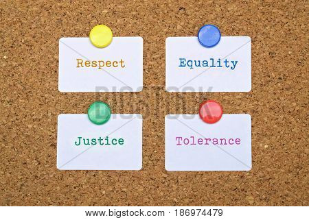 Words Equality and Justice written on four white stickers pinned on cork board